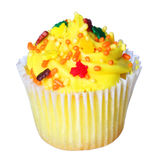 Cupcake with yellow frosting and colored sprinkles isolated on white. Royalty Free Stock Images