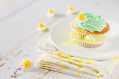 Cupcake with yellow ribbon, white wood background Stock Images