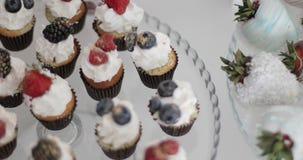Cupcakes με τα φρέσκα μούρα σε ένα πιάτο γυαλιού φιλμ μικρού μήκους