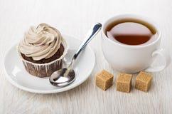 Cupcakes με την καφετιά κρέμα, κουταλάκι του γλυκού στο πιατάκι, φλυτζάνι του τσαγιού Στοκ Εικόνες