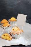 Cupcakes με την κενή ετικέττα στον ξύλινο πίνακα Στοκ Εικόνες