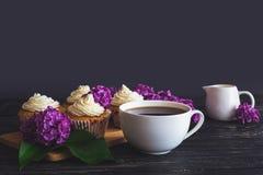 Cupcakes με την κρέμα, τον καφέ και τα λουλούδια Στοκ Φωτογραφίες