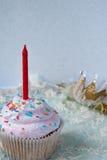 Cupcakes με το κόκκινο κερί στα πρώτα γενέθλια ενός μικρού κοριτσιού Στοκ Φωτογραφία