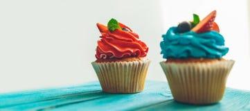 Cupcakes σε ένα μπλε εκλεκτής ποιότητας ξύλινο υπόβαθρο Στοκ Εικόνα