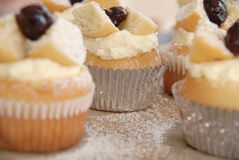 Cupcakes. Fairy cupcakes filled with cream and topped with a dollop of cherry jam.  An example of old fashioned baking, set off by the worn board Stock Photo