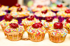 Cupcakes. Decorated cupcakes with cherries and colored sugar sprinkles Royalty Free Stock Photography