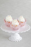 Cupcakes. With a swirl of vanilla buttercream frosting and pink decor on stand for the cake Royalty Free Stock Images