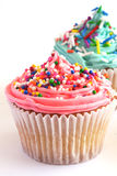 Cupcakes. Two cupcakes one frosted in pink the other in blue both topped with colorful candy sprinkles royalty free stock images