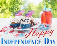 Cupcakes with american flags on independence day. Celebration, independence day and holidays concept - close up of glazed cupcakes decorated with american flags stock photography
