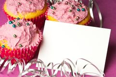 Cupcakes with a blank invitation Royalty Free Stock Photography