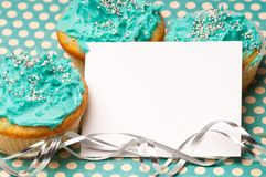 Cupcakes with a blank invitation Stock Photos