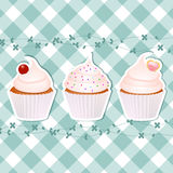 Cupcakes on blue gingham. Three cupcakes on blue gingham with floral border Royalty Free Stock Image