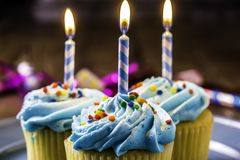 Cupcakes and Burning Birthday Candles Royalty Free Stock Images