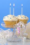 Cupcakes With Candles. Cupcakes on glass stand with lit candles and streamers, gift in background Royalty Free Stock Photography