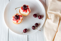 Cupcakes with cherries on plate Royalty Free Stock Photos