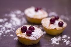 Cupcakes with cherries and powdered sugar on a dark wooden table stock image