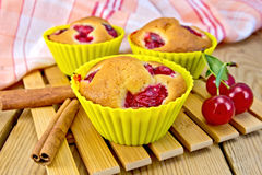Cupcakes with cherries in tins on board Royalty Free Stock Photography