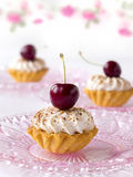 Cupcakes with cherries and whipped cream. Three cakes with cherries and whipped cream Stock Image