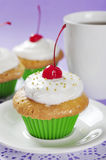 Cupcakes with cherry. Cupcakes with whipped cream and cherry on violet background Stock Photo