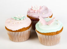 Cupcakes with colorful sweet lilies and butterfly Royalty Free Stock Image