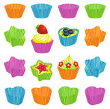 Cupcakes and colourful baking cups. Set of cupcakes and colourful cupcake baking cups Stock Photography
