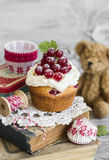 Cupcakes with cottage cheese cream and red currants and toy bear Stock Photo