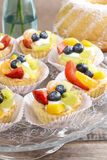 Cupcakes with cram and fresh fruits Stock Photography