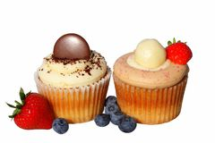 Cupcakes with cream and berries. Chocolate and strawberry cupcakes decorated with cream and berries isolated on white Stock Photography