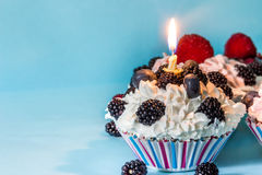 CUPCAKES WITH CREAM AND BERRIES, WITH A LIGHTED CANDLE ON BLUE BACKGROUND Royalty Free Stock Images