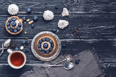 Cupcakes with cream and blueberries,meringues and tea. Top view,copy space. Royalty Free Stock Image