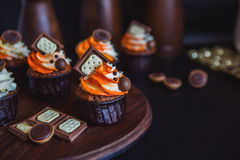 Cupcakes with cream in a dark glass, decorated with chocolate, biscuits stand on a stand of dark wood on a dark background Stock Image