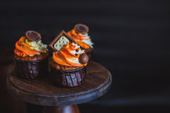 Cupcakes with cream in a dark glass, decorated with chocolate, biscuits stand on a stand of dark wood on a dark background Stock Images