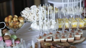 Cupcakes with cream and macaroon cookies on a beautiful sweets table stock video footage