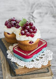 Cupcakes with cream and red currants on a light wooden background Royalty Free Stock Image