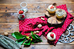 Cupcakes with cream and strawberry chocolate and nuts on a woode. N background stock photos