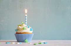 Cupcakes with cream and sugar butterflys and birthday candle Royalty Free Stock Image