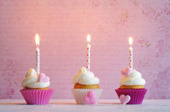 Cupcakes with cream and sugar hearts and birthday candle Stock Images