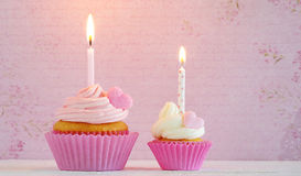 Cupcakes with cream and sugar hearts and birthday candle Royalty Free Stock Image