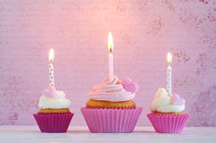Cupcakes with cream and sugar hearts and birthday candle Stock Image