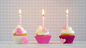Cupcakes with cream and sugar hearts and birthday candle Royalty Free Stock Images