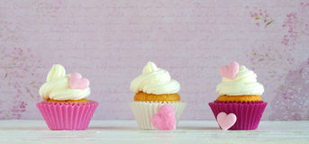 Cupcakes with cream and sugar hearts Stock Photo
