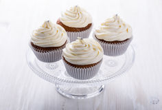 Cupcakes with creamcheese frosting. Homemade cupcakes with creamcheese frosting on cake stand on light background royalty free stock photos