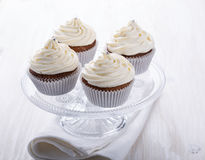 Cupcakes with creamcheese frosting. Homemade cupcakes with creamcheese frosting on cake stand on light background stock images