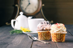 Cupcakes and cup of tra on dark wooden background Royalty Free Stock Image