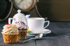 Cupcakes and cup of tra on dark wooden background Stock Image