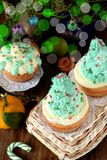 Cupcakes decorated as Christmas fir trees on a wicker basket surrounded by festive attributes Stock Images
