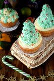 Cupcakes decorated as Christmas fir trees on a wicker basket surrounded by festive attributes Stock Photos