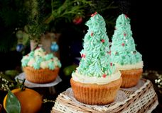 Cupcakes decorated as Christmas fir trees on a wicker basket surrounded by festive attributes Royalty Free Stock Image