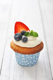Cupcakes decorated with and fresh berries. Cupcakes decorated with butter cream and fresh berries in polka dot cases on wooden background Royalty Free Stock Photography