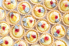 Cupcakes decorated with fresh fruits. pitaya, pineapple and melon. Stock Photography